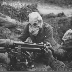 Machine gunners in action wearing gas helmets