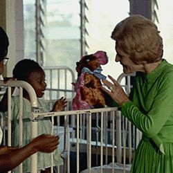 Mrs. Nixon visits with a child in a hospital in Ghana