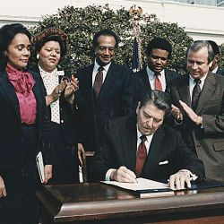 Photograph of President Reagan and the Signing Ceremony for Martin Luther King Holiday Legislation