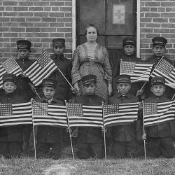 Very early class of young boys with flags at the Albuquerque Indian School