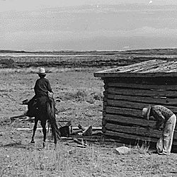 [Navajo man on a horse and another by a log cabin house on the Navajo reservation.]