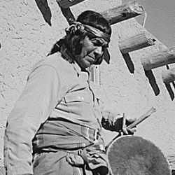 "Indian descending wooden stairs with drum, another in background looking on, ""Dance, San Ildefonso Pueblo, New Mexico, 1942"