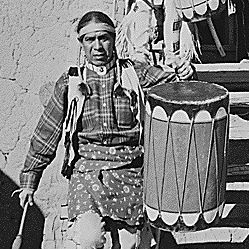 "Two Indians descending wooden stairs, carrying drums; another Indian and child near by, ""Dance, San Ildefonso Pueblo, New Mexico, 1942"