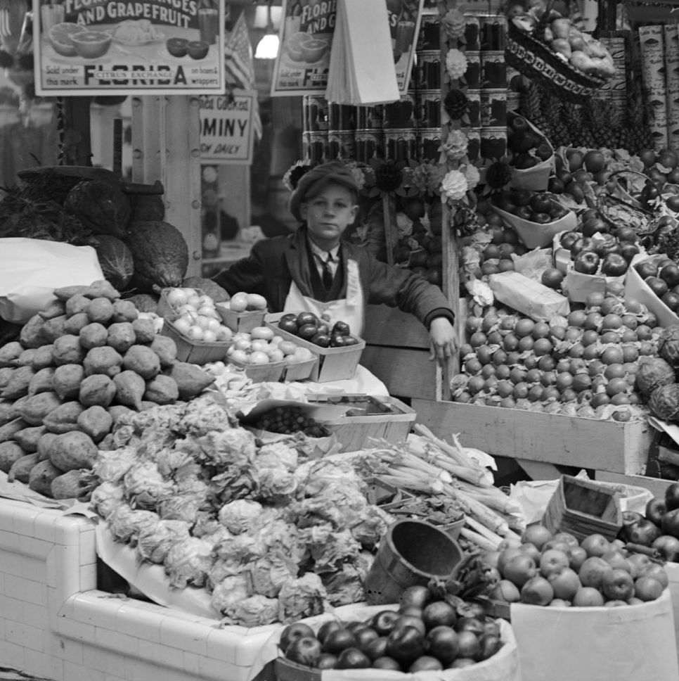 Young boy tending freshly stocked fruit and vegetable stand at Center Market