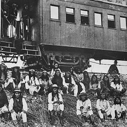 Chiricahua Apache prisoners, including Geronimo seated on an embankment outside their railroad car, Arizona