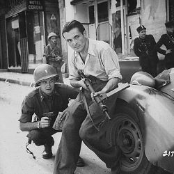American officer and French partisan crouch behind an auto during a street fight in a French city.