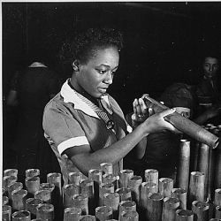 """Bertha Stallworth, age 21, shown inspecting end of 40mm artillery cartridge case at Frankford Arsenal."""