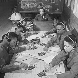 """Basic and advanced flying school for Negro Air Corps cadets, Tuskegee, Alabama... In the center is Capt. Roy F. Morse, Air Corps... He is teaching the cadets how to send and receive code."""