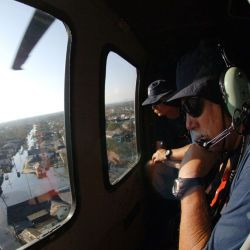 [Hurricane Katrina] New Orleans, LA, September 7, 2005 - FEMA Urban Search and Rescue members look through the windonw of a Blackhawk helicopter to search for residents in areas impacted by Hurricane