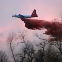 "[Severe Wildfire Threat] Ratliff, OK, January 18, 2006 -- A Lockheed P2 V5 ""Neptune"" airplane drops its load of 2080 gallons of fire retardant just before air operations are ceased due to darkness. Si"