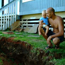 [Earthquake] Kapaau, HI, October 25, 2006- Oliver Kolly with son Oliver inspect the changed landscape in their backyard after a series of earthquakes struck this region. Adam DuBrowa/FEMA.