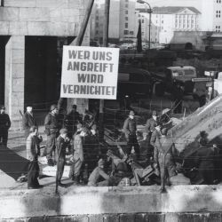 "[Translated Title] Banner Says ""Whoever Attacks Us Will Be Destroyed"". Example of an East German Confrontational Propaganda Banner Produced By the Volksarmee and Volkspolizei"