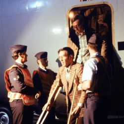 Major Dave Marten (on crutches) exits a C-141 Starlifter aircraft upon his arrival from Tehran, Iran