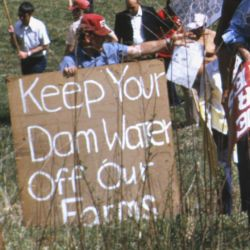 Residents with Signs Standing on Location of Proposed Dam