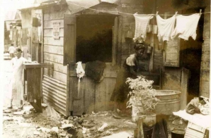 Woman Washing Clothes Outside a Shack