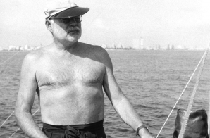 Ernest Hemingway at the wheel of his boat, Pilar, with Havana in the background, Cuba.